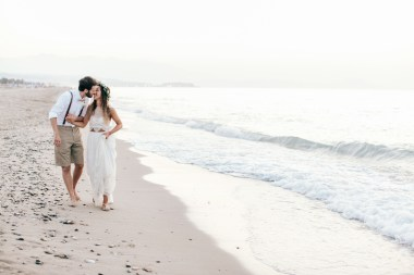 Professional image of bride and groom walking along the seashore on a sandy beach in Crete after their beach wedding ceremony.