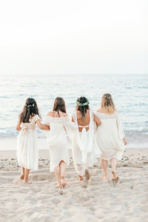 Professional group portrait of the bride and her bridesmaids having fun on the beach after the formalities of the wedding ceremony.