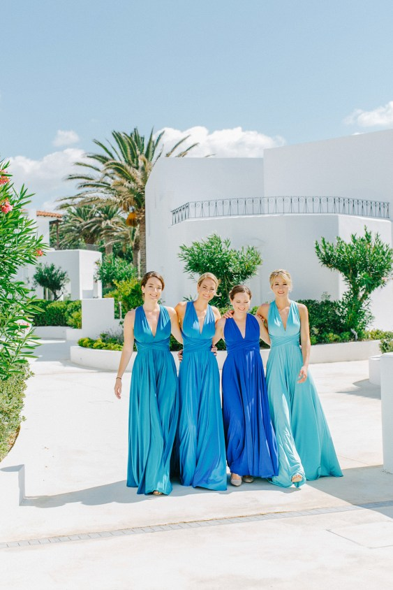 Professional portrait of four bridesmaids walking along Caramel hotel wearing mismatched dresses and looking at the wedding photographer smiling.