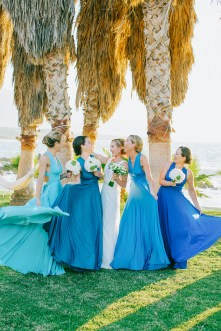 Wedding day portrait of bride and bridesmaids having fun after the wedding ceremony wearing white Pronovias bridal dress and blue mismatched dresses by Two Birds bridal boutique and holding flower bouquets.