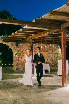Groom and bride walking during their grand entrance for dinner reception at Grecotel Agreco wedding estate in Crete, smiling and waving towards the guests and the wedding photographer.