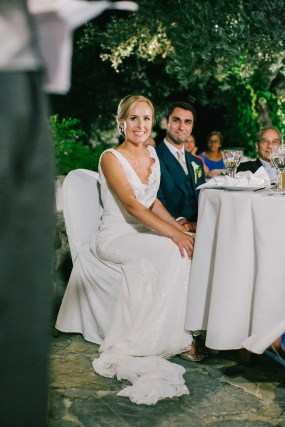 Groom and bride sitting at the head table and listening to speeches during dinner reception at Grecotel Agreco wedding estate in Crete, smiling.