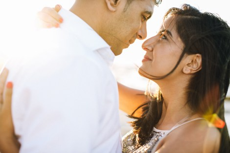 Close up portrait of an engaged couple posing on the beach in Crete during their pre wedding engagement photosession at sunset.