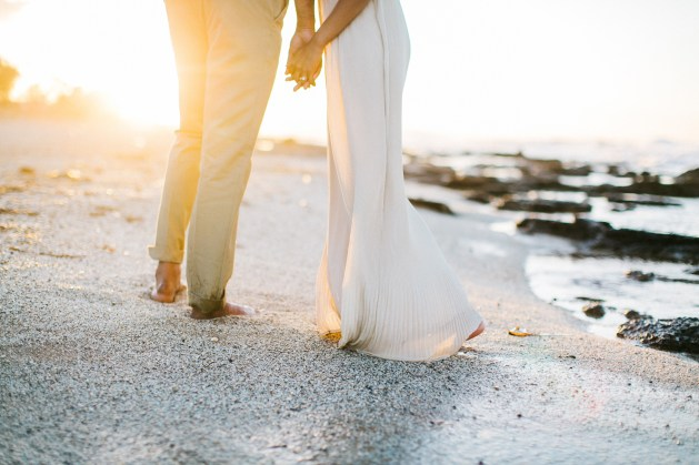 Close up photo of young couple holding hands when posing on the beach in Crete during their pre wedding engagement photosession at sunset.