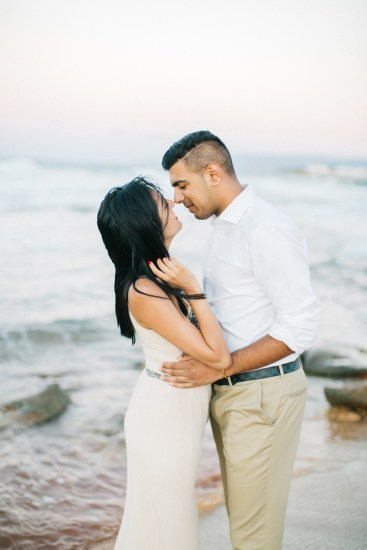 Engaged couple posing for portraits on a stunning sandy beach in Crete during professional pre wedding engagement photoshoot.