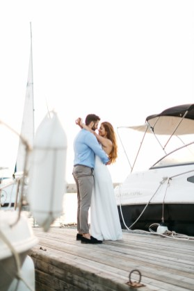 beautiful couple posing for professional photographer in the port of Chania Crete with sunset background of old harbor, surrounded by luxury yachts.