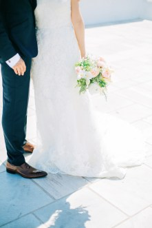Professional Santorini wedding day photoshoot, close up photograph of groom and bride's outfits and the wedding bouquet taken in front of the church in Oia.