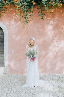 Elegant classy bride posing for wedding day bridal portraits holding flowers in Chania, Crete.