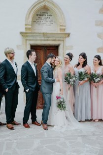 Beautiful newlywed couple with group of their friends posing for the wedding photographer on a summer wedding in Chania, Crete.
