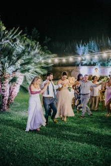 Bride and groom dancing traditional Greek dances on an exclusive wedding night in Metohi Kindelis, Chania, Crete photographed by professional photographer team.