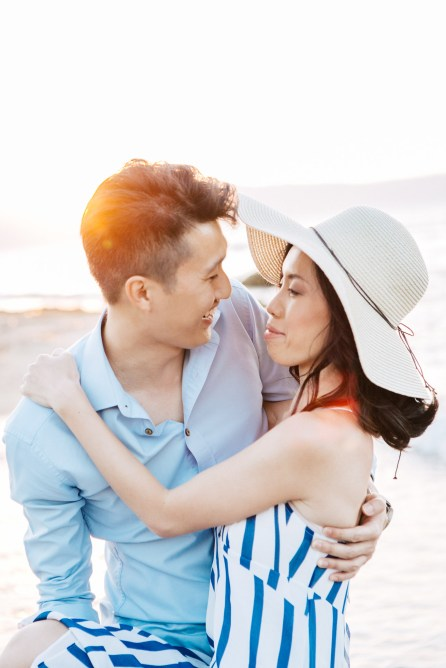 Happy international couple wearing summer clothing is posing for professional photographer team during their beach wedding photoshoot on the secluded shores of Rethymno town, Crete, Greece.