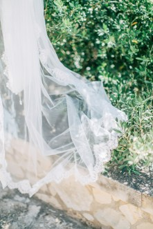 Detail of intricate bridal veil photographed on an olive tree background.