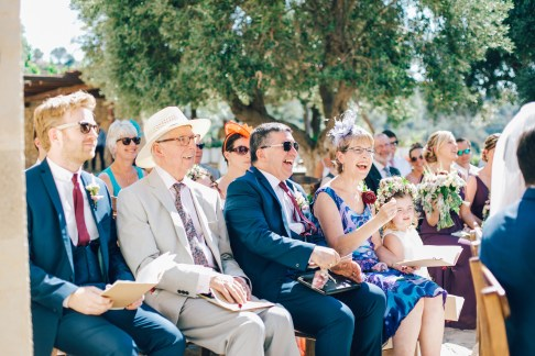 Candid image of a happy reaction of the wedding guests crowd on a destination wedding day in Agreco Farm in Crete, Greece, captured by wedding photographer. Guests are smiling and laughing.