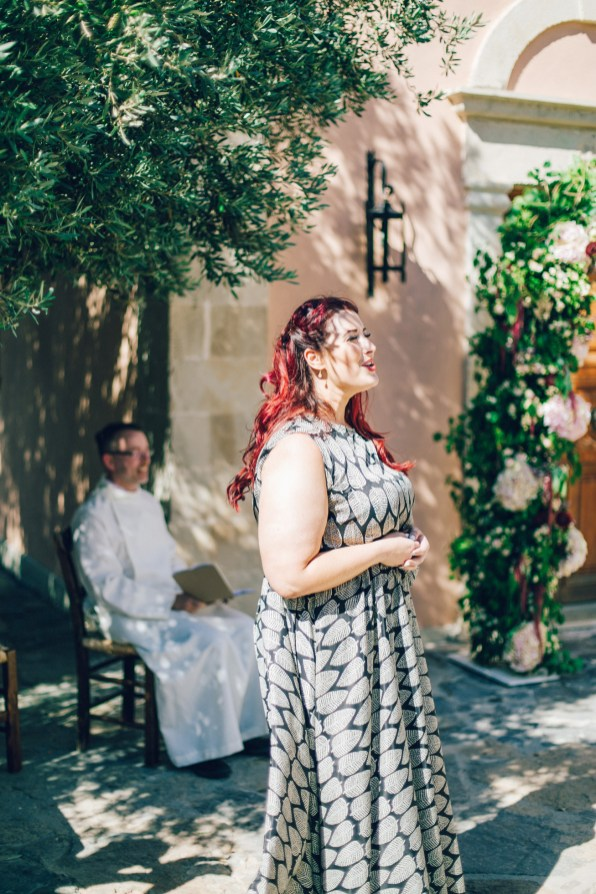 Candid image of a wedding singer performing for the newlyweds on a destination wedding day in Agreco Farm in Crete, Greece, captured by wedding photographer.
