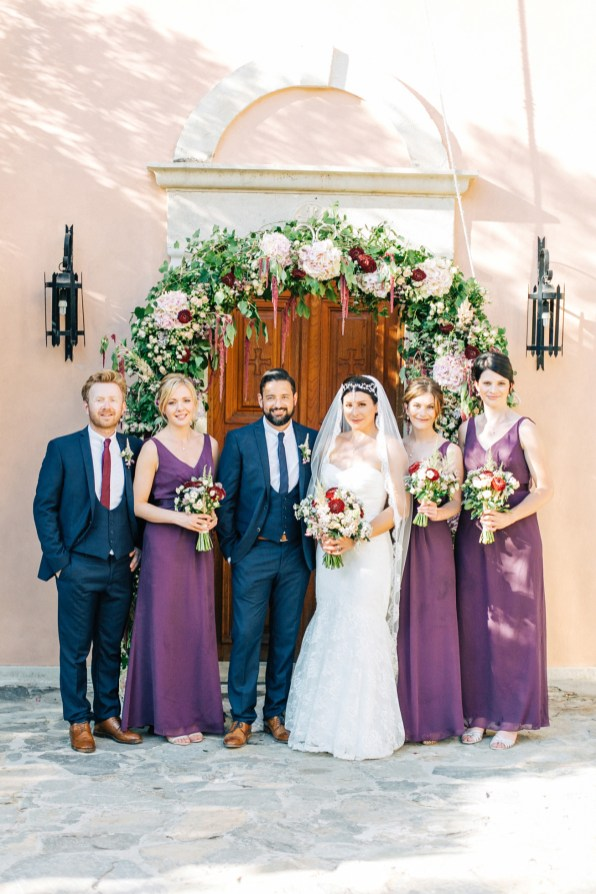 Classy bride and groom and their party posing for formal portraits after the wedding ceremony at Agreco Farm in Crete, Greece.