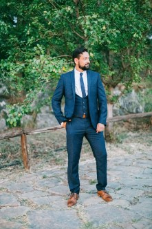 Elegant classy groom posing for portraits for his photographer on a destination wedding day in Agreco Farm, Crete.
