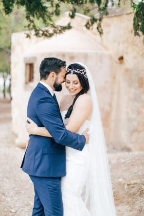 Fine art wedding portraits of the newly wedded couple posing for professional destination wedding photographer at Fortezza of Rethymno in Crete, Greece.