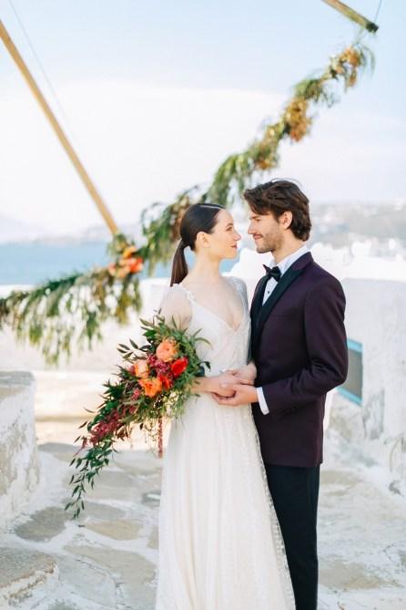 Stylish bride and groom on their destination wedding in Mykonos, posing under the windmills.