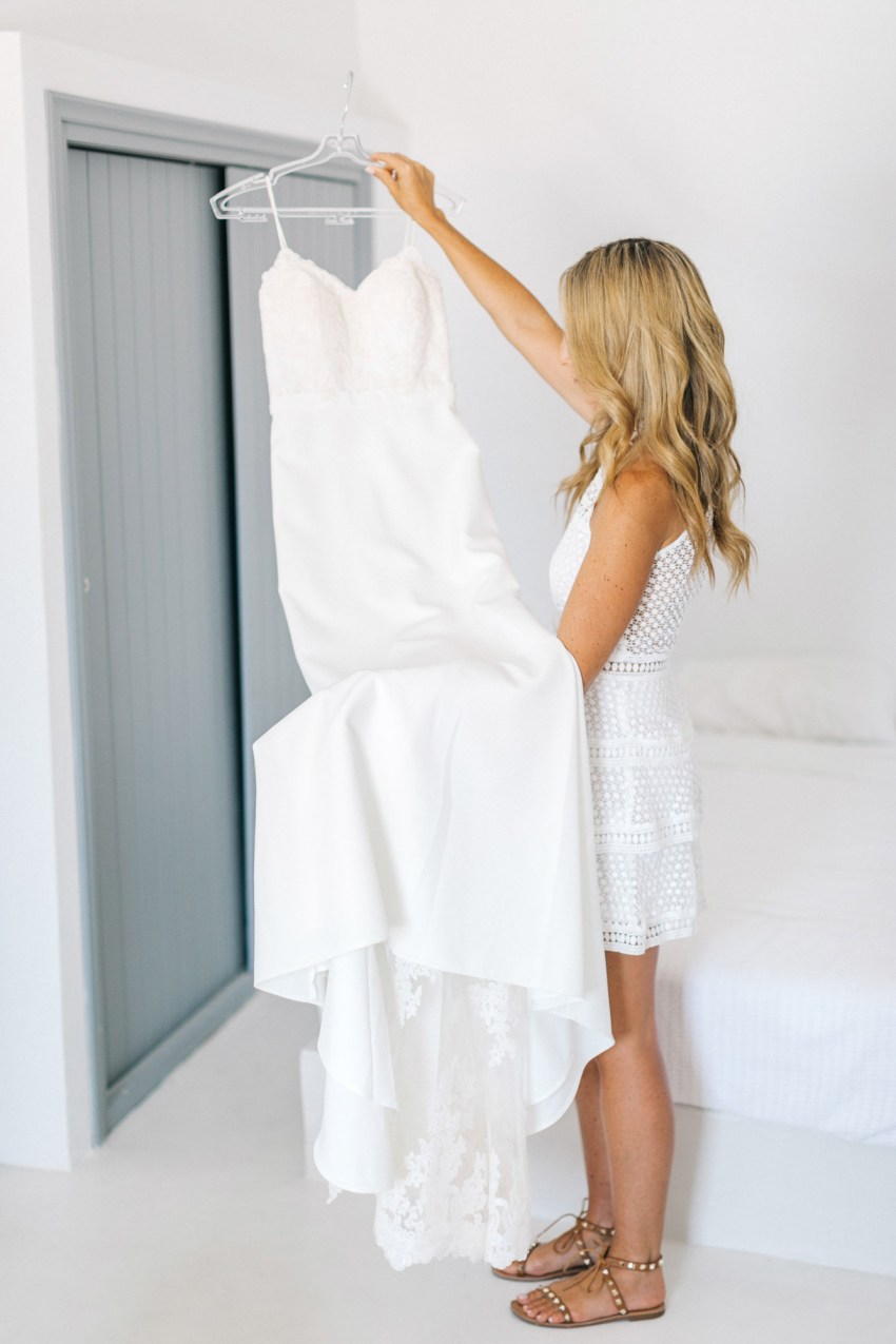 Bride holding her dress in Santorini villa.