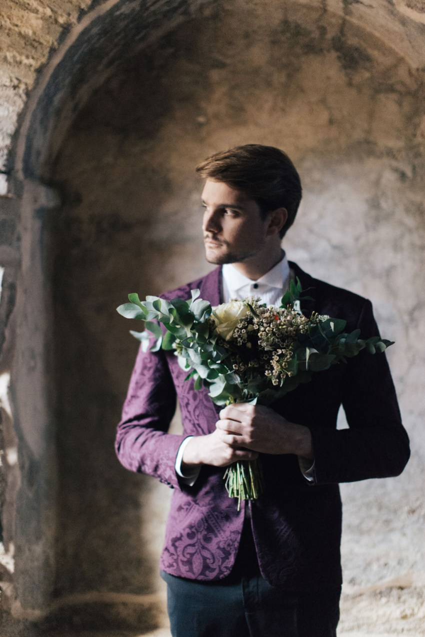 Groom wearing fancy suit and styled for wedding in Greek islands