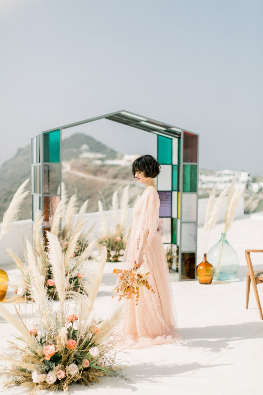 Dreamy and poetic Santorini bride wearing flowy designer wedding dress and diamond theme coordinated jewellery.