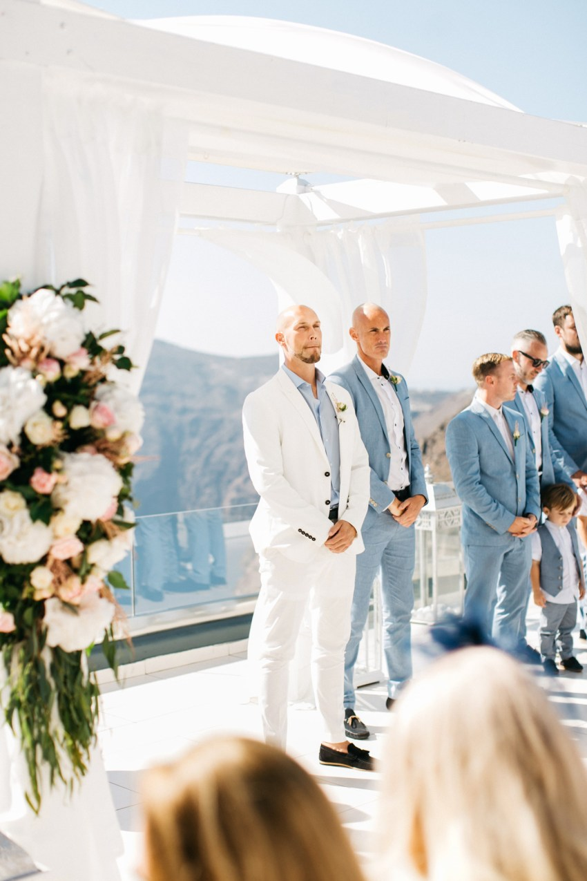 Groom waiting for the bride under a wedding canopy at Le Ciel wedding estate in Santorini island, Greece.