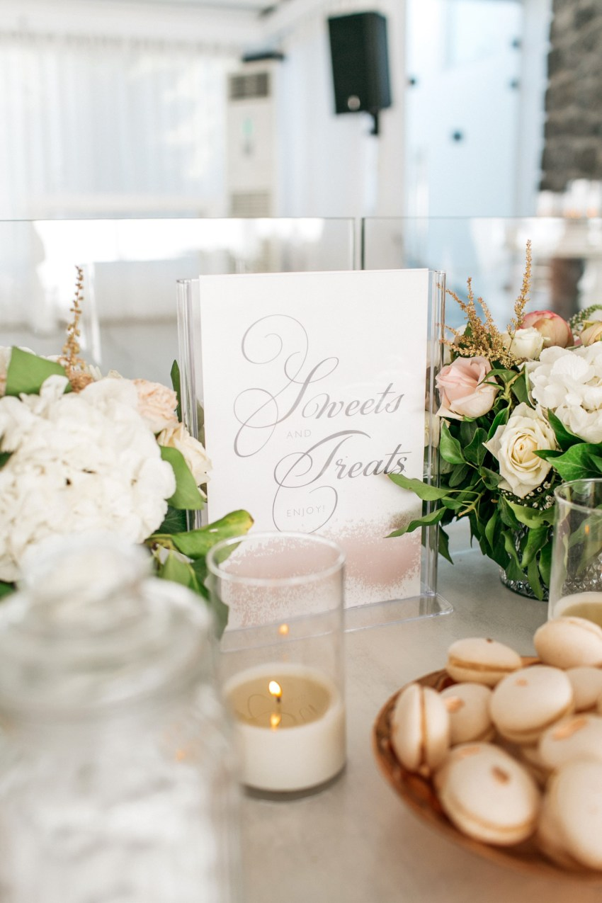 Wedding dinner details and reception decoration in white and blush pink including the sweets table at Le Ciel wedding estate in Santorini island, Greece.