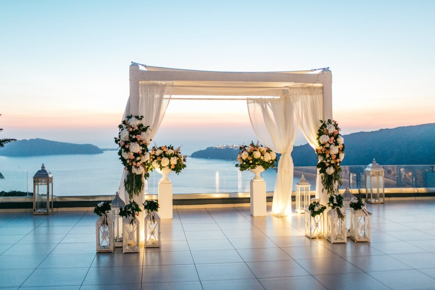 Sunset wedding canopy decoration and setup at Le Ciel wedding estate in Santorini island, Greece.