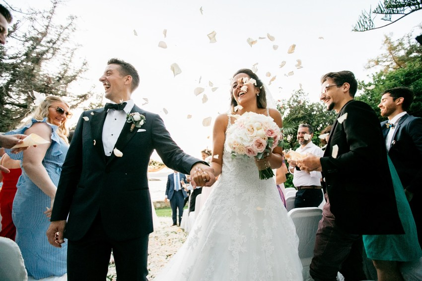 Beautiful international couple after their destination wedding ceremony in Chania Crete Greece walking down the isle and being showered with flower petals.