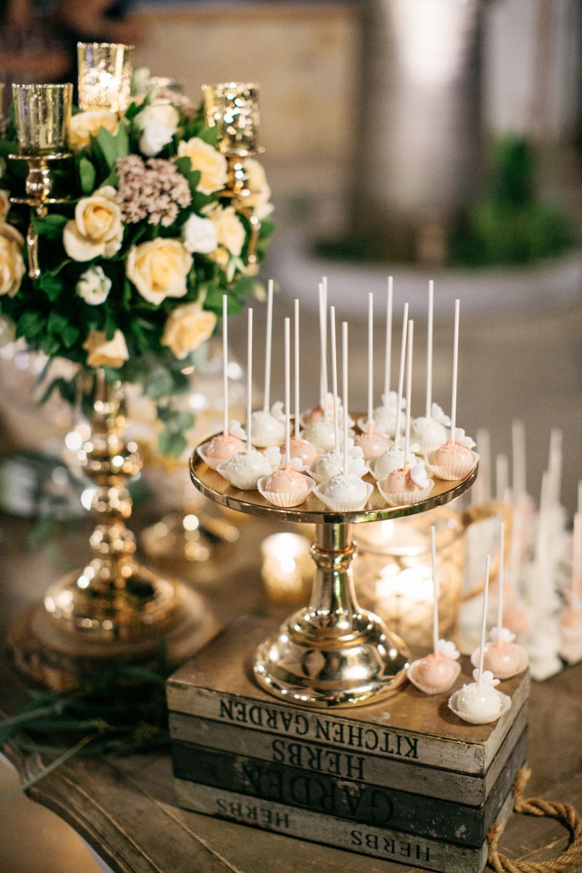 An elegant wedding sweets table with rich florals and intricate details in gold and pink in Chania Crete Greece.