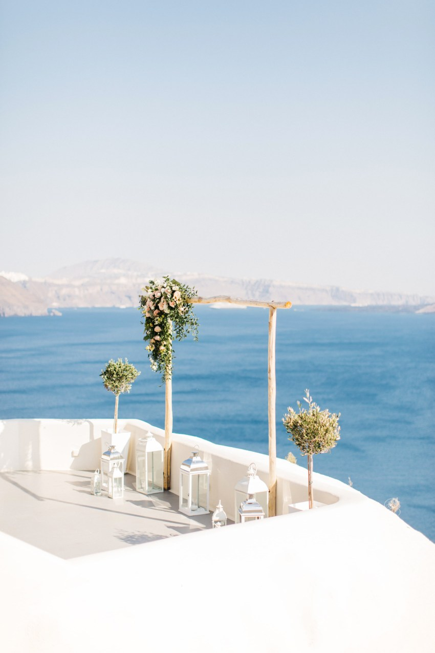 Flowery wedding arch and ceremony setup in Canaves Suites Oia Santorini.