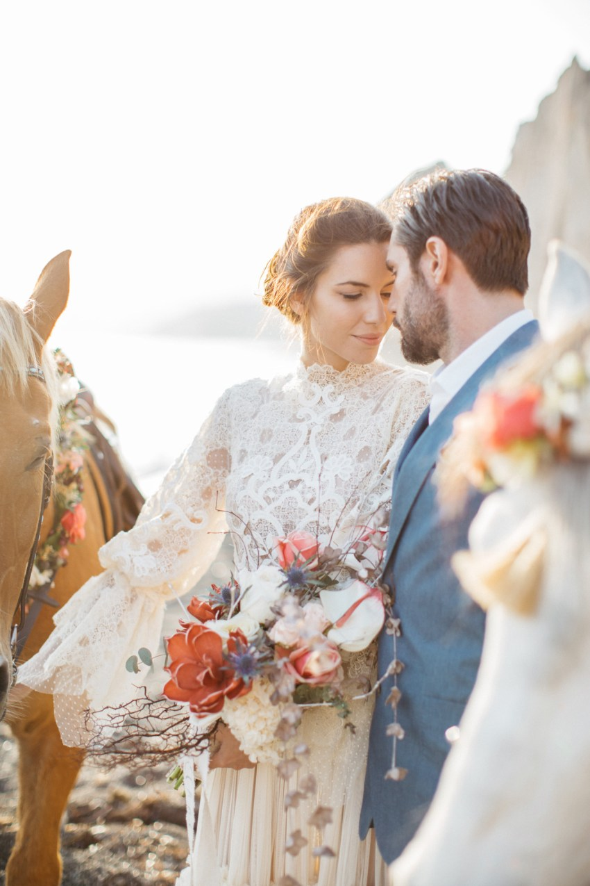 Beautiful romantic bride and groom with horses at a volcanic beach wedding inspiration session in Santorini Greece.
