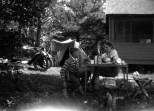 An unidentified boy sits outside of a cottage near Hayward, Wis., with Ruby V. (Treutel) Hanneman (1904-1977) in July 1925. Ruby and new husband Carl F. Hanneman (1901-1982) were on their honeymoon.