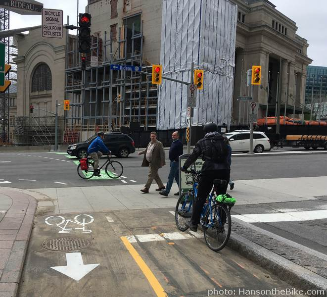 The yellow dots in the pavement trigger your light. Stay there, else they revert back to red without giving you a chance to cross. If you want to turn right, turn left (!) and wait in the bike box on Rideau st