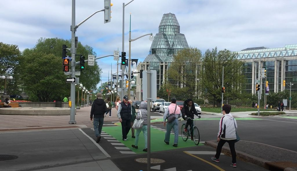 Basically everything goes wrong here: peds in bike lane, cyclist avoiding ped, taking wrong lane, unclear cross walk on the left not being used.