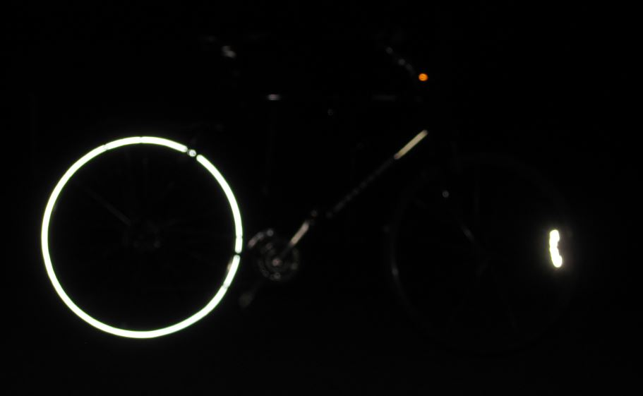 My bike with one reflective tire and one without. This is lit up by our porch light. The difference is serious.