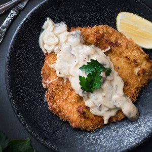 Pork Schnitzel with Mushroom Gravy - Battered, tender pork, fried until golden-brown and topped with a creamy mushroom gravy!