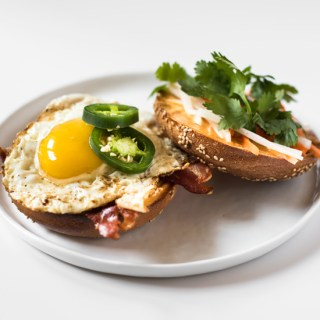 This Breakfast Bánh Mì is a bagel topped with bacon, a fried egg, Sriracha-mayo, do chua, sliced jalapeno, and cilantro. Bring lots of napkins!