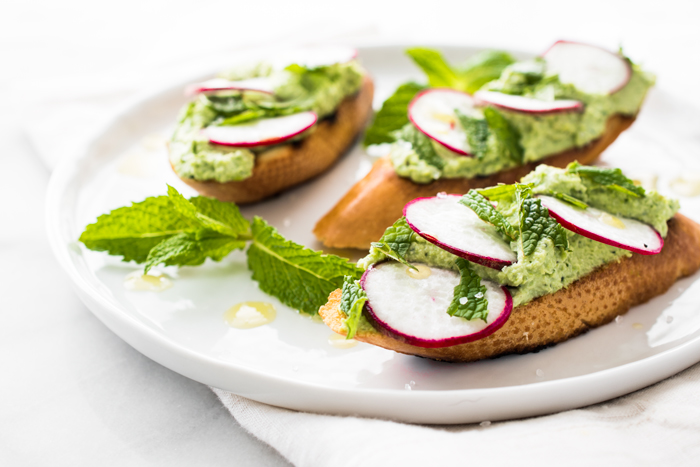 Edamame & Ricotta spread with thinly sliced radishes, mint, and sea salt on toasted bread. Ready for snacking in about 10 minutes!
