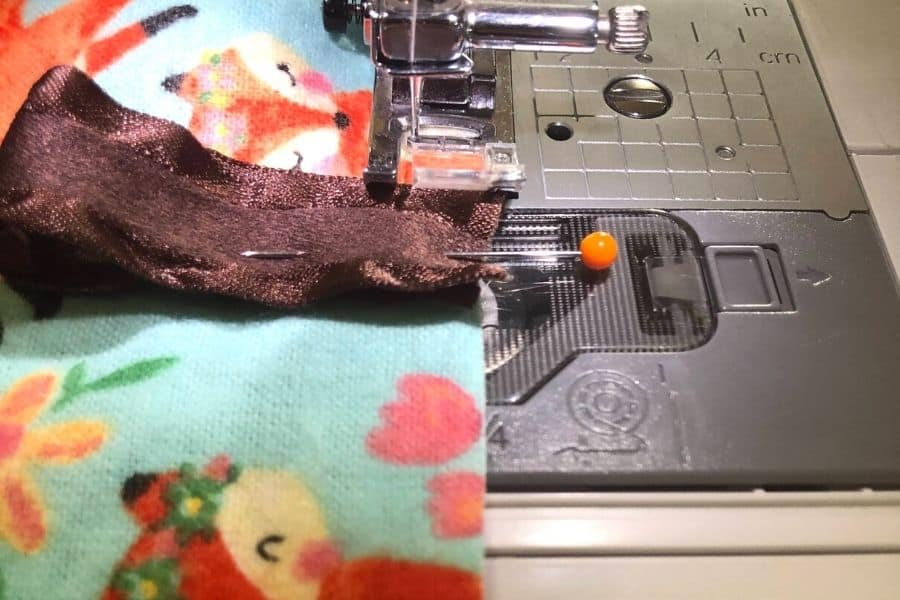 sewing on the ribbon with the sewing machine