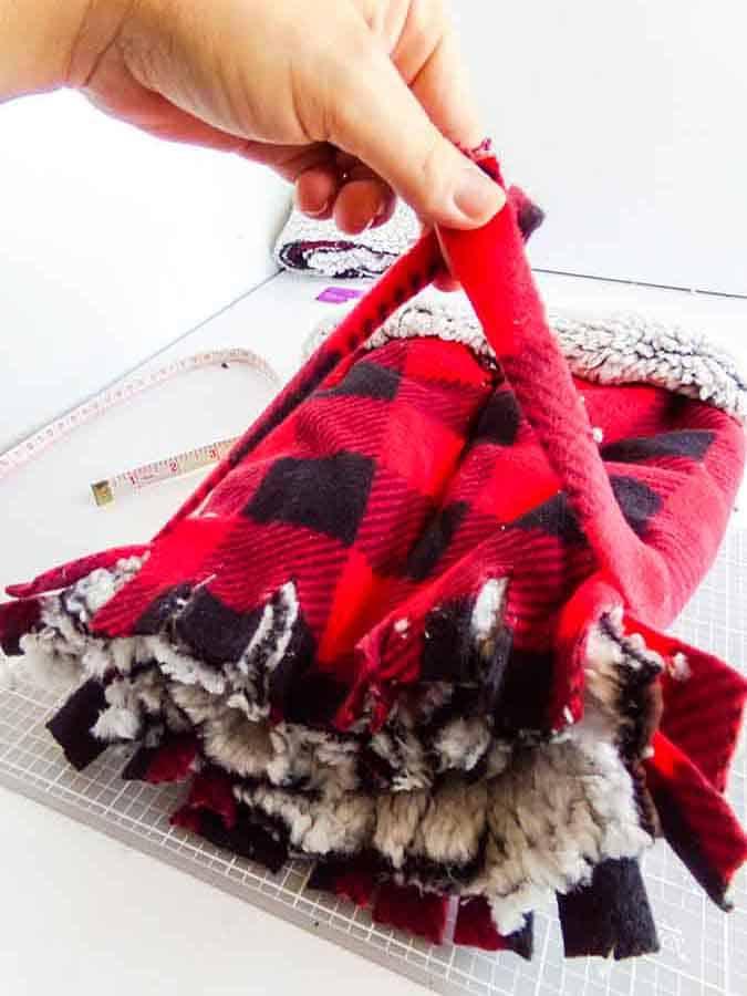 tying pom poms for No-Sew Fleece Hat