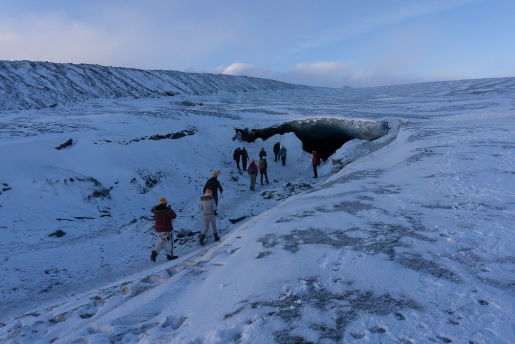 A tour group makes their way towards the mouth of an ice cave in Iceland. The Ultimate Guide to Ice Caves in Iceland: Everything you ever needed to know about visiting ice caves in Iceland. Find out how to go INSIDE the Crystal Cave glacier ice cave to see the blue ice.