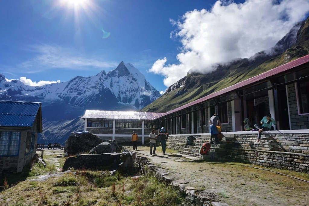 Trekkers pack their bags outside the teahouse at Annapurna Base Camp. What to pack for the Annapurna Base Camp Trek in Nepal.