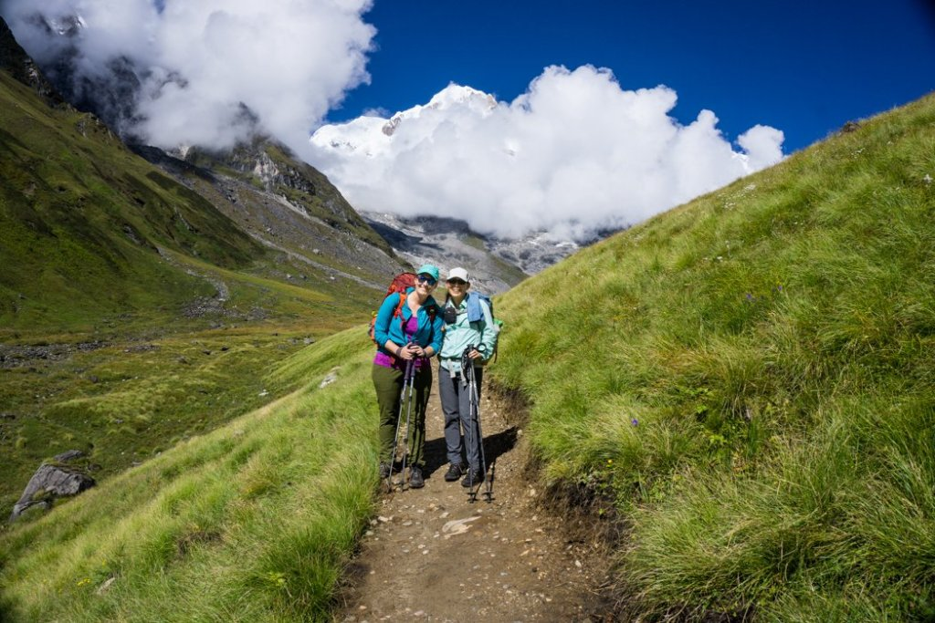 Two trekkers pose on the trail on the way down from Annapurna Base Camp. What to pack for the Annapurna Base Camp Trek in Nepal.