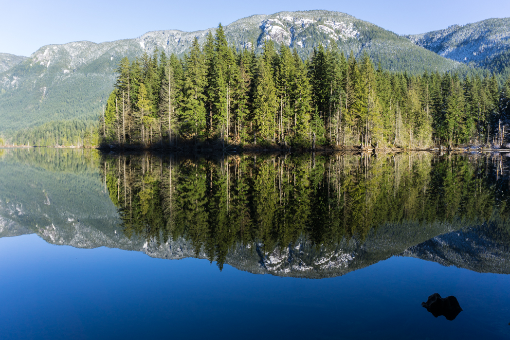 Mountains reflected in a lake on a quiet hiking trail. Don't like crowds? Here are 15 ways to avoid crowded hiking trails.
