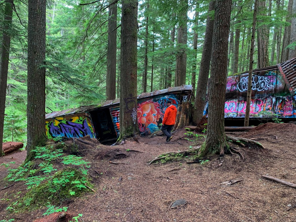 A hiker explores abandoned train cars on the Whistler Train Wreck Trail