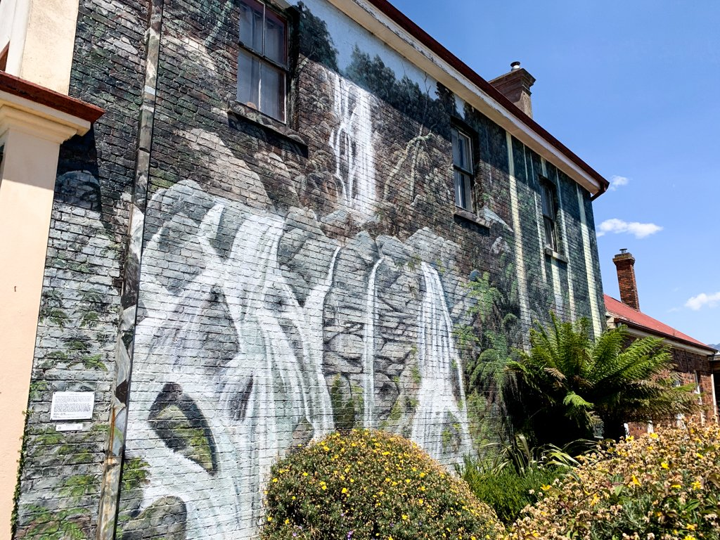 A mural of a waterfall painted on the side of the brick building in the small town of Sheffield, Tasmania