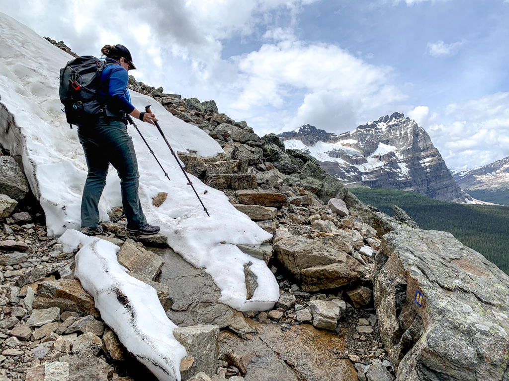 A hiker walking through snow with trekking poles on the All Soul's Alpine Route at Lake O'Hara in Yoho National Park