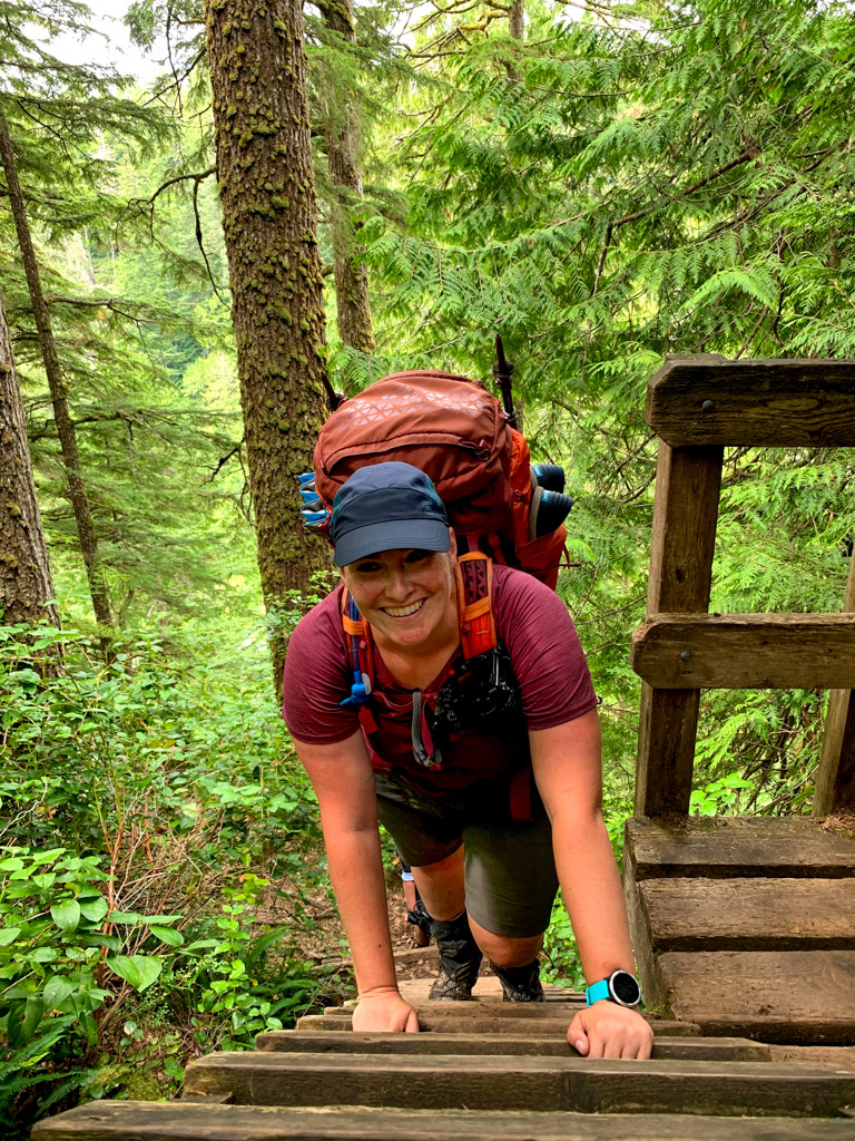 A hiker climbs a ladder on the West Coast Trail