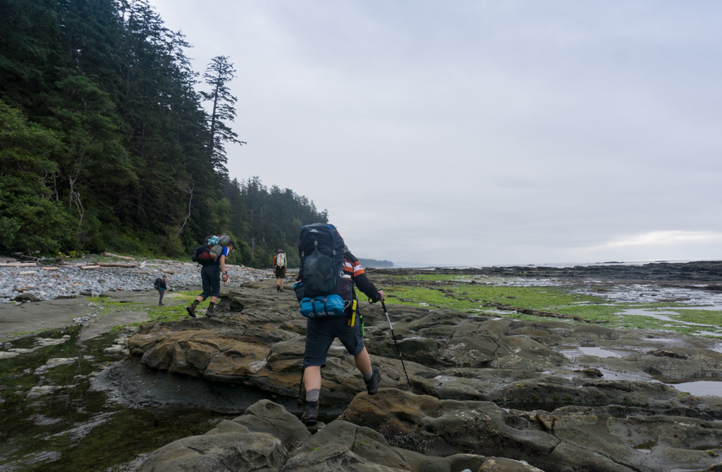 Hikers walking on the rocky coastal shelf near Michigan Creek on the West Coast Trail